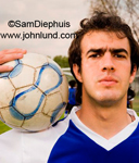 Futbol player portrait of a male futbol player holding a ball on his shoulder.  Blue and white uniform. Player looking at camera.